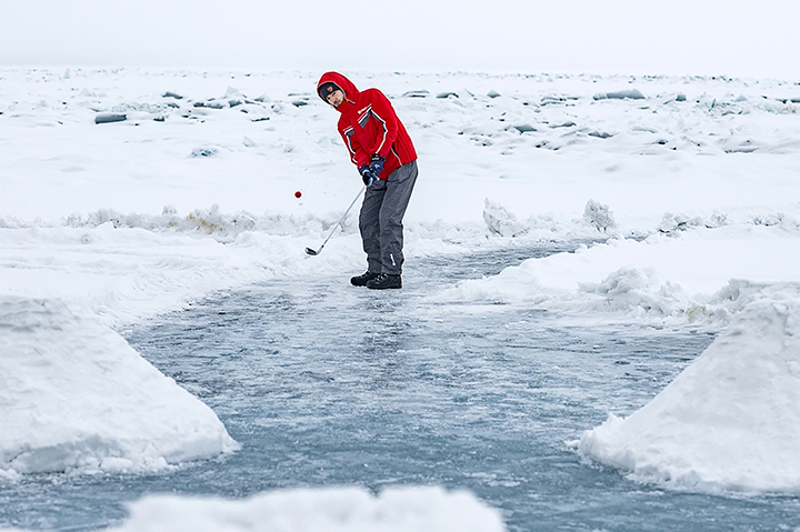Teeing off for golf contest on frozen surface world's deepest lake