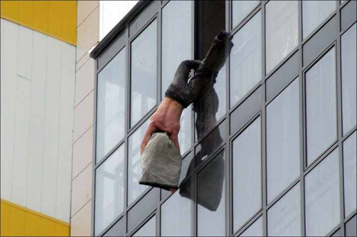Man hanging in window