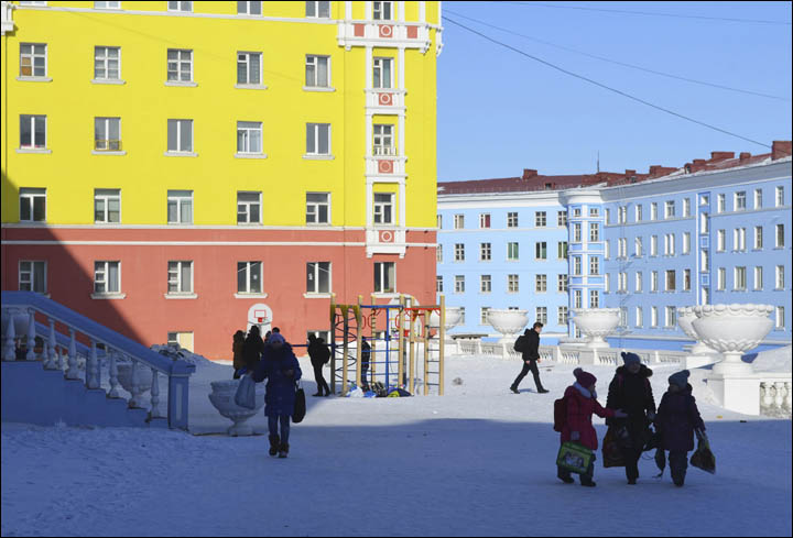 Children walking along colorful buildings