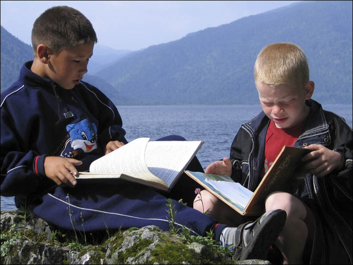 Boys reading the books on the Teletskoye lake